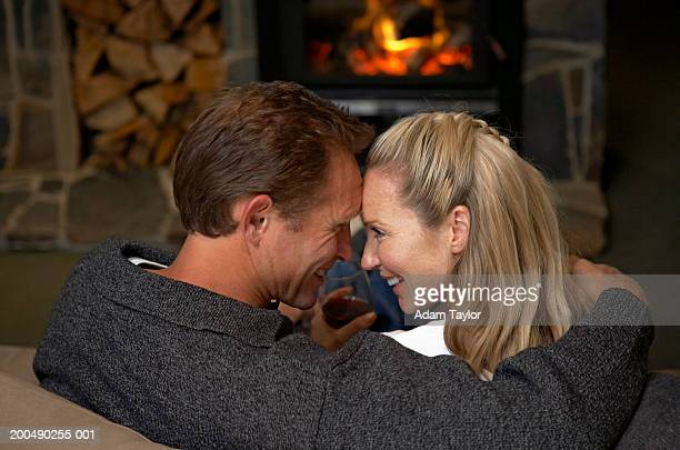 Mature couple embracing by fireplace, smiling, side view
