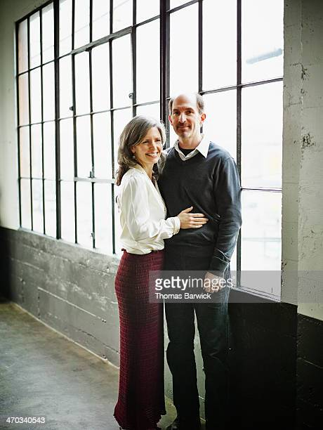 Mature couple embracing by windows in loft space