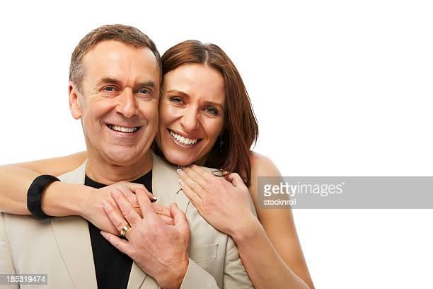 Älteres Paar umarmen einander und Lächeln in die Kamera.