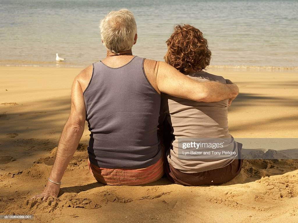Mature couple embracing on beach, rear view : Stock Photo