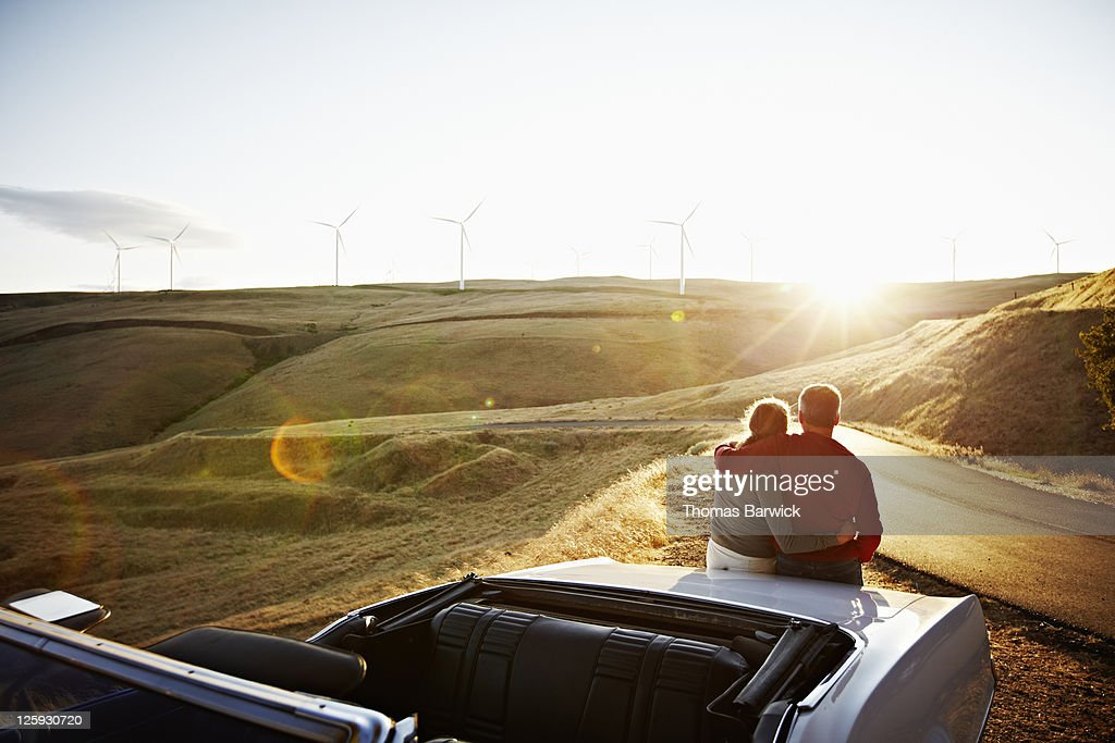 Mature couple embracing on car watching sunset : Stock Photo