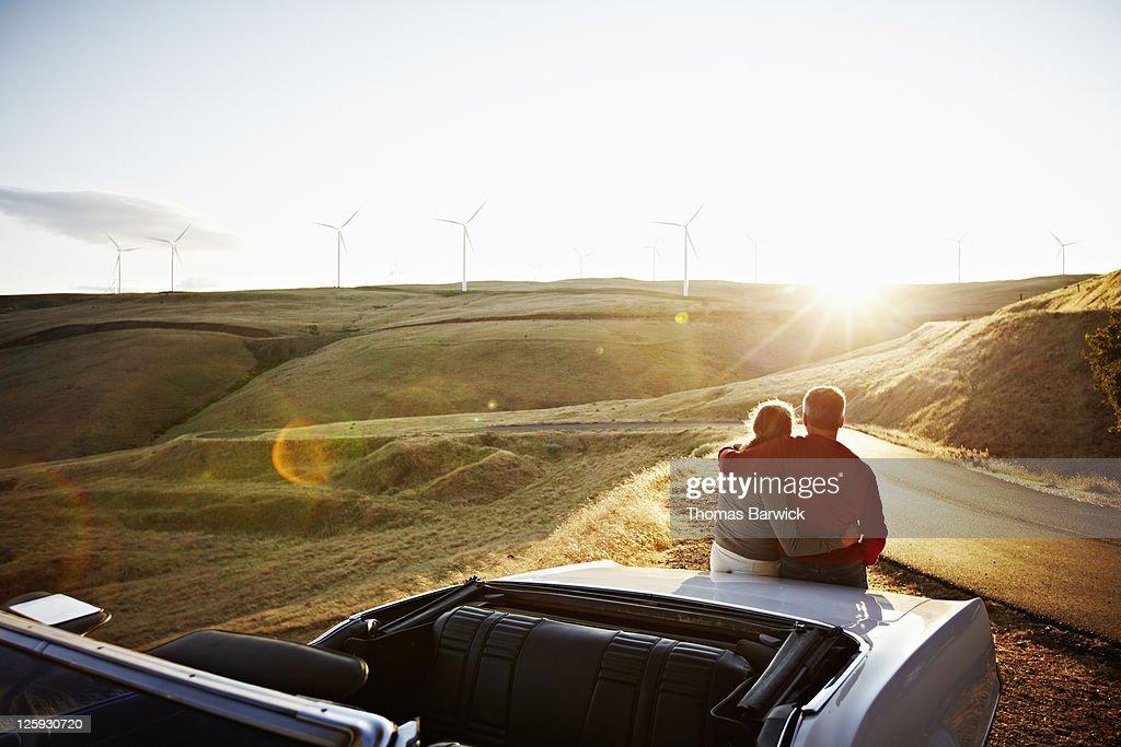 Mature couple embracing on car watching sunset