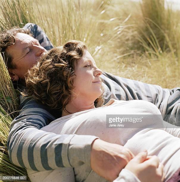 Mature couple embracing on grass, close-up
