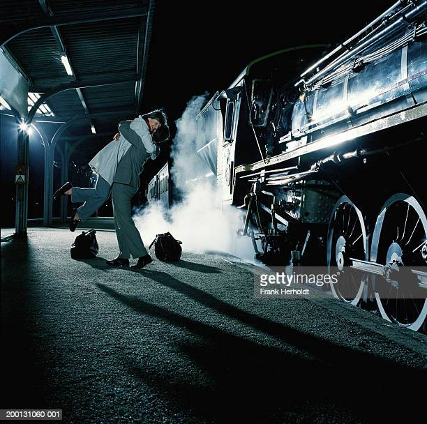 Mature couple embracing on platform by steam train, man lifting woman