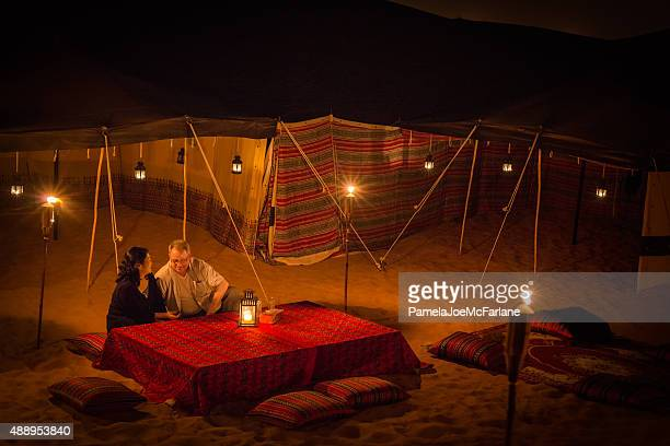 Mature Couple Enjoying Arabian Desert Camping with Lanterns and Torches