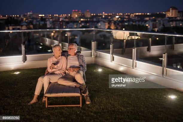 Mature couple appréciant le soir avec verre de vin sur leur balcon d'appartement.