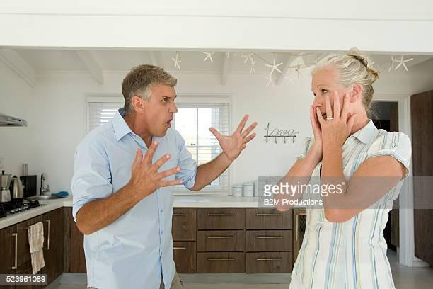 Mature couple fighting on kitchen