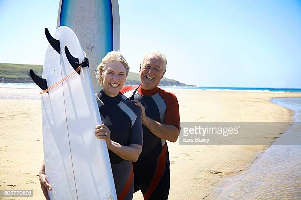 A mature couple going surfing on a beach