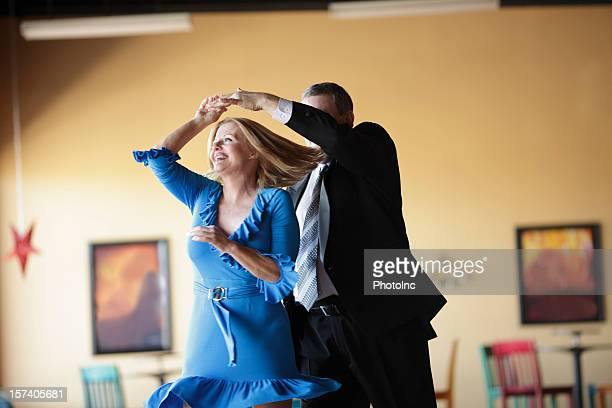 Mature couple happily ballroom dancing indoors