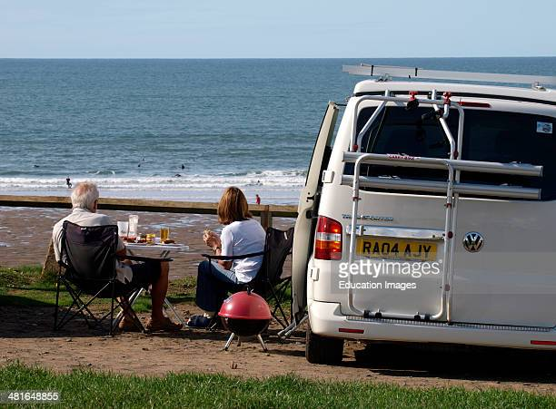 Mature couple having a BBQ next to their VW transporter van Widemouth Bay Bude Cornwall UK