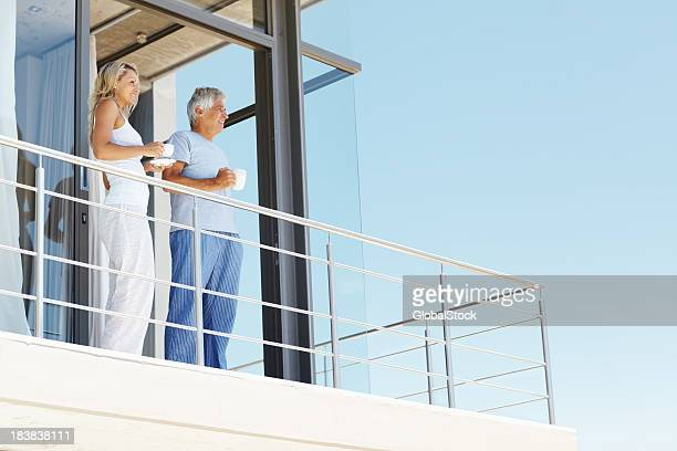 Mature couple having coffee at the balcony