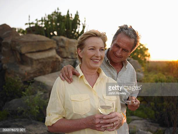 Mature couple having drinks in rocky landscape, smiling, sunset