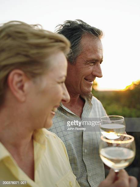 Mature couple having drinks outdoors, smiling, sunset (focus on man)