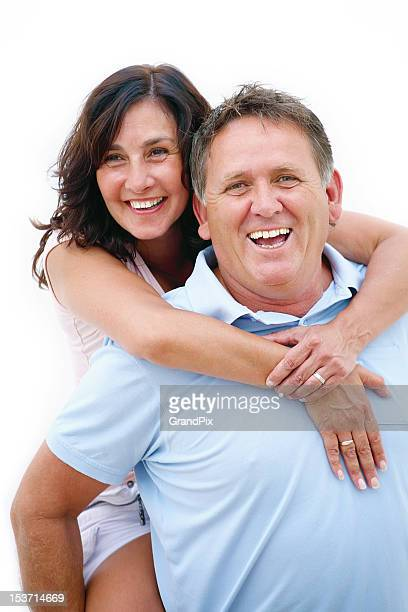 Mature couple having fun giving piggy back ride