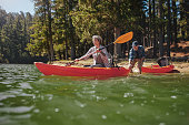 Portrait of mature woman canoeing in the lake with man about to catch the kayak from behind. Senior couple having fun kayaking in the lake.