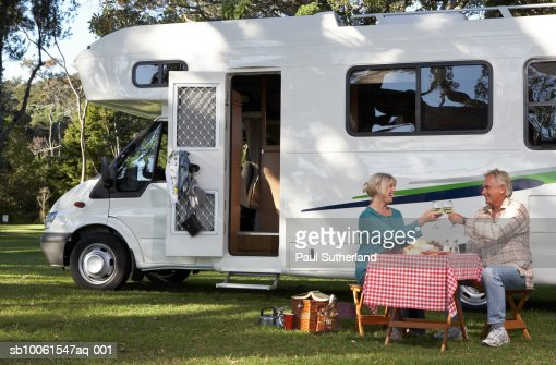 Mature couple having picnic by motor home in park, toasting : Foto stock