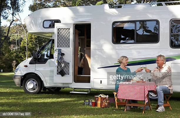 Mature couple having picnic by motor home in park, toasting