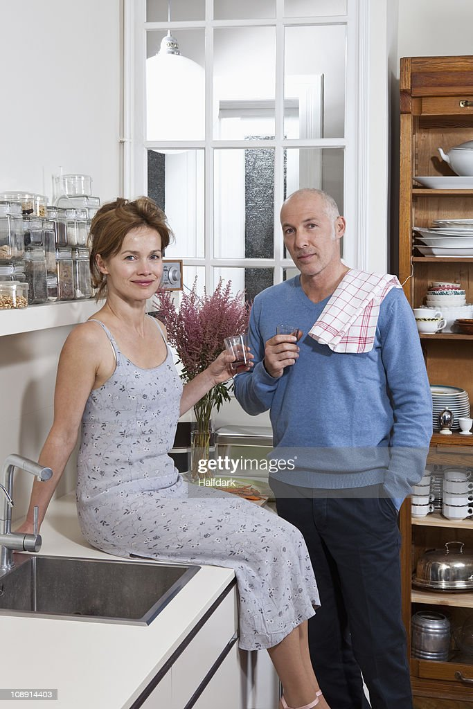 A mature couple having red wine together in their kitchen : Stock Photo