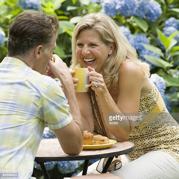 Mature couple having tea in a lawn and laughing