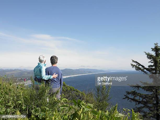 Mature couple hiking by sea, smiling