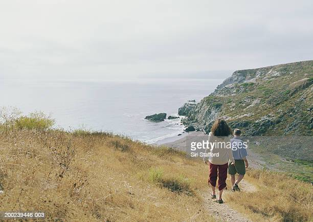 Mature couple hiking down bluff towards beach
