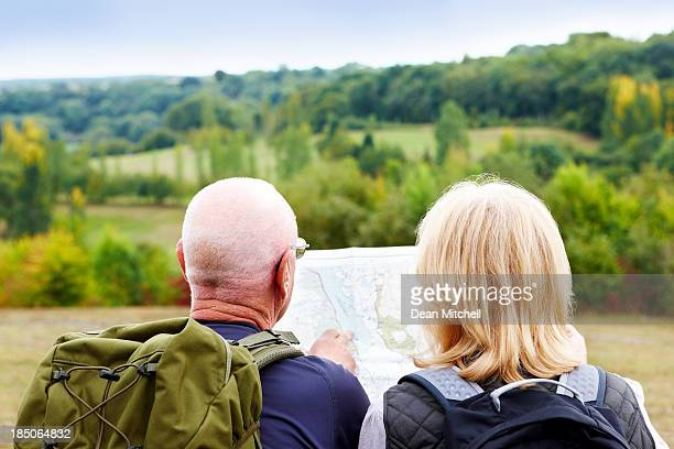 Mature couple hiking looking at map for directions