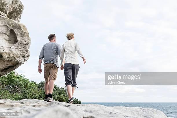 Matura coppia escursioni sulle rocce con le mani, Bondi Beach