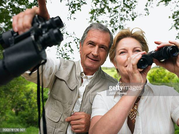 Mature couple holding binoculars, man pointing ahead, smiling