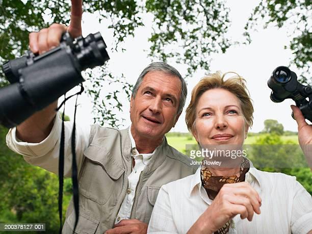 couple d'âge mûr tenant jumelles, homme souriant pointant vers le haut,
