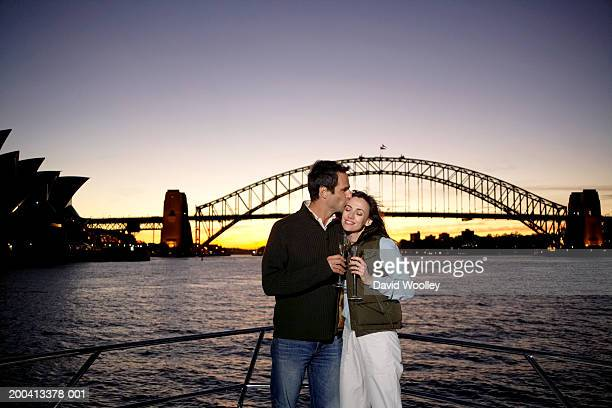 Mature couple holding drinks  on yacht, man kissing woman, sunset