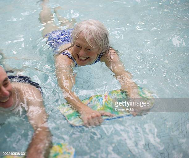 Mature couple holding floats, swimming in pool, smiling