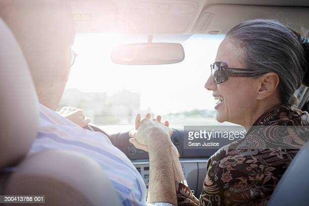 Mature couple holding hands in car, rear view, close-up