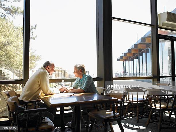 Couple d'âge mûr tenant mains dans le restaurant