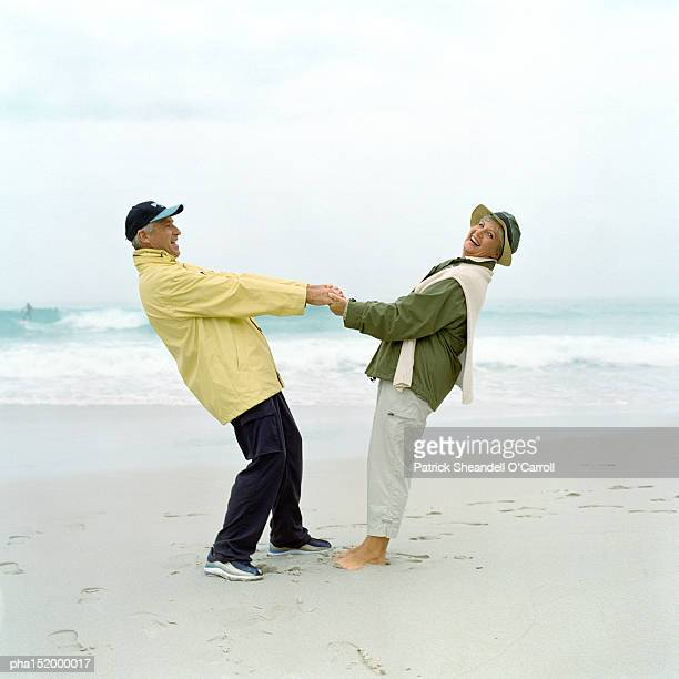 Mature couple holding hands on beach.