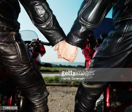 Mature couple holding hands on motorcycles, rear view