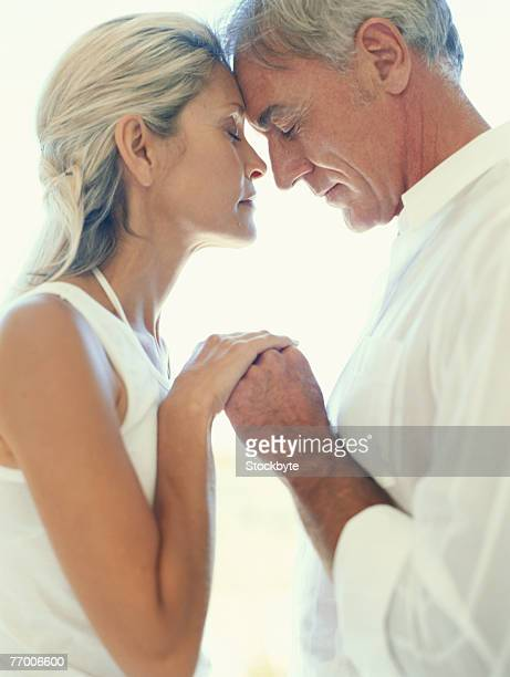 Mature couple holding hands, side view