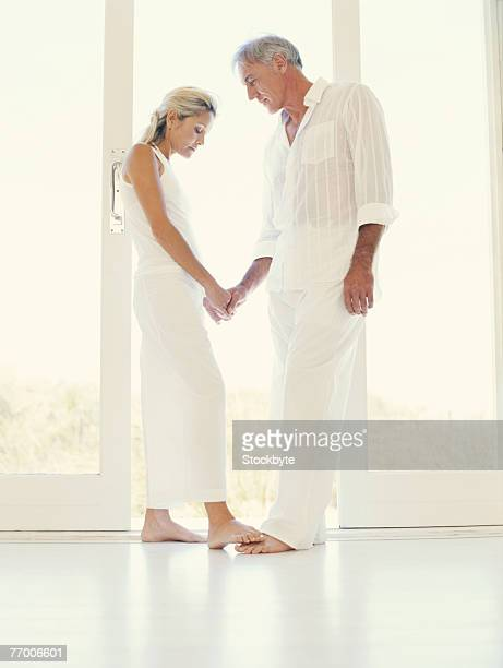 Mature couple holding hands standing at doorway, side view
