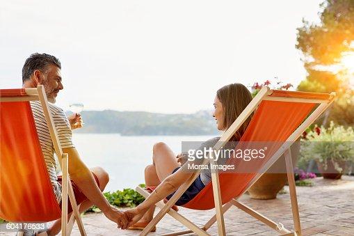 Mature couple holding hands while enjoying wine