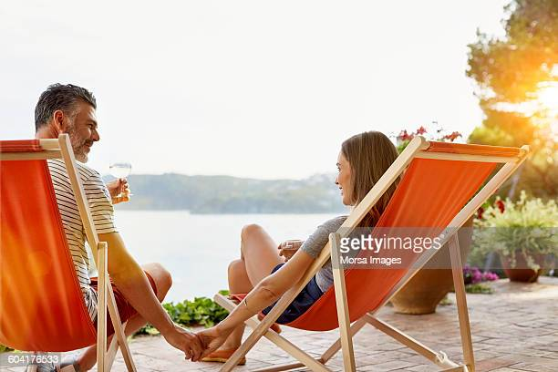 Mature couple holding hands while enjoying wine