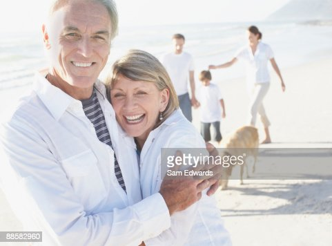 Mature couple hugging on beach with family : Stock Photo