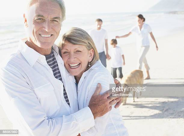 Mature couple hugging on beach with family