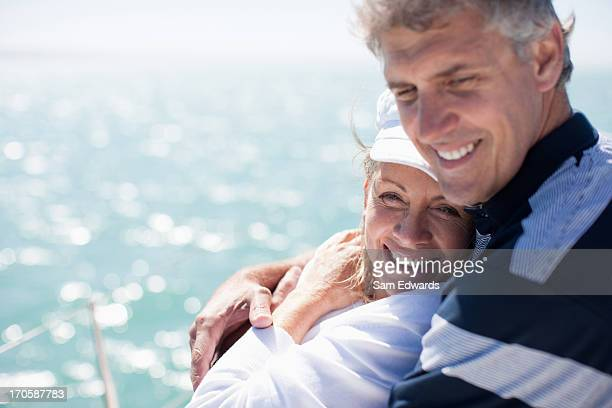 Mature couple hugging on boat