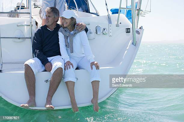 Mature couple hugging on deck of sailboat