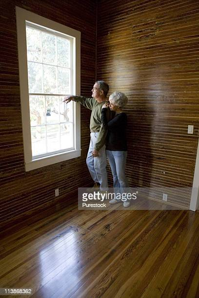 Mature couple in a darkened room leaning against window, gazing out