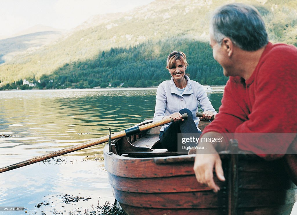 Mature Couple in a Rowing Boat on a Lake, Woman Rowing : Stock Photo