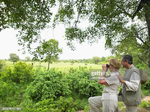 Mature couple in African bush, woman using binoculars, side view