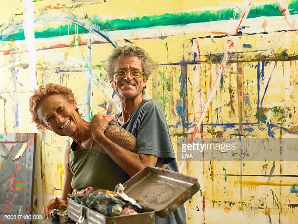 Mature couple in art studio smiling, portrait