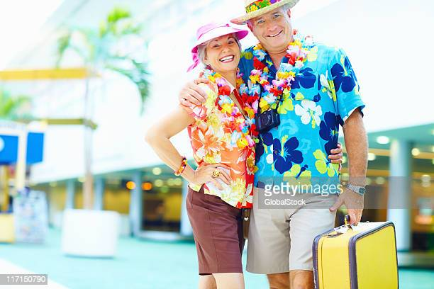 Mature couple in floral clothing with luggage at an airport