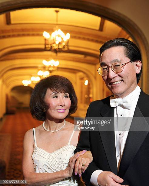 Mature couple in formal attire, standing in lobby of theater, portrait