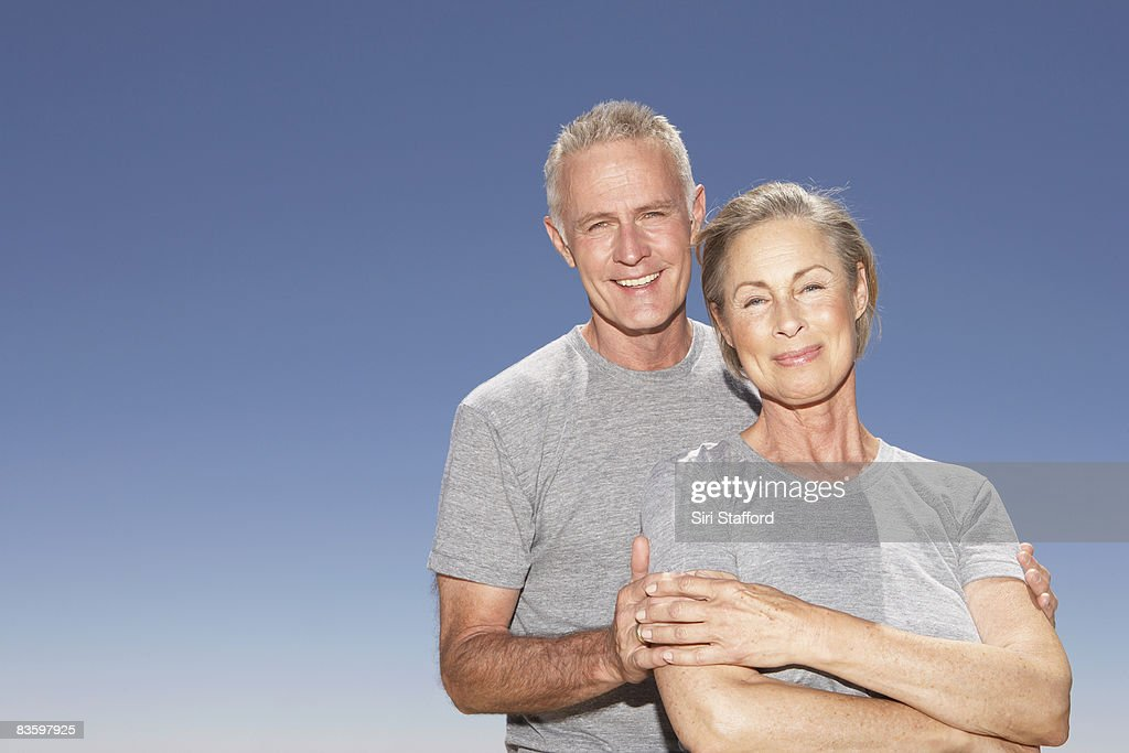 Mature Couple in gray tshirts smiling at camera : Stock Photo